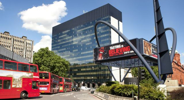 daytime view of Old Street roundabout with red london bus going past
